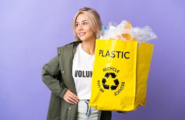 Junge russische frau, die eine recycling-tasche voll papier hält, um lokalisiert auf lila, das mit armen an der hüfte und lächelnd aufbereitet zu recyceln