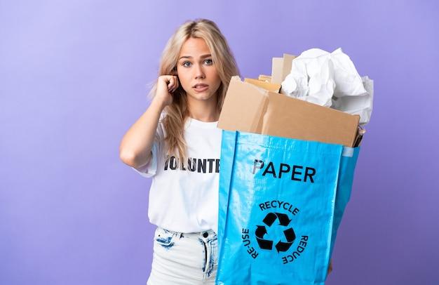 Junge russische frau, die einen recyclingbeutel voll papier hält, um isoliert auf lila frustriert und bedeckenden ohren zu recyceln