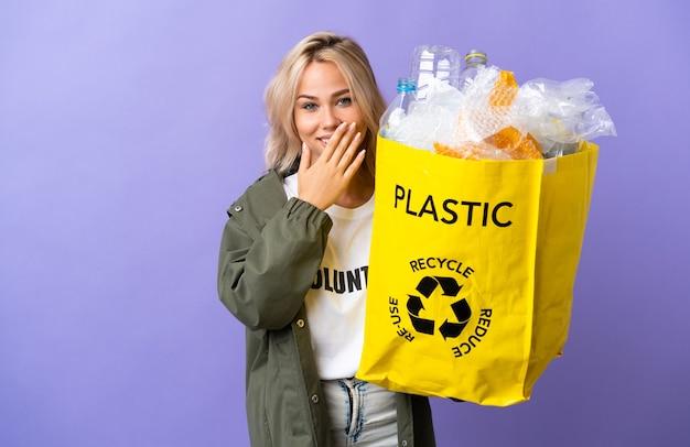 Junge russische frau, die einen recyclingbeutel voll papier hält, um lokalisiert auf lila wand glücklich und lächelnd zu bedecken mund mit hand zu recyceln