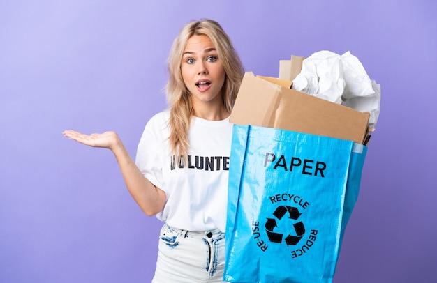 Junge russische frau, die einen recyclingbeutel voll papier hält, um lokalisiert auf lila wand mit schockiertem gesichtsausdruck zu recyceln
