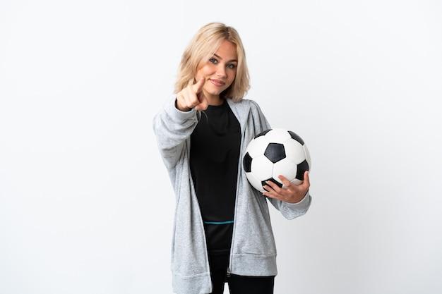 Junge russische frau, die fußball lokalisiert auf weißer wand zeigt, zeigt front mit glücklichem ausdruck