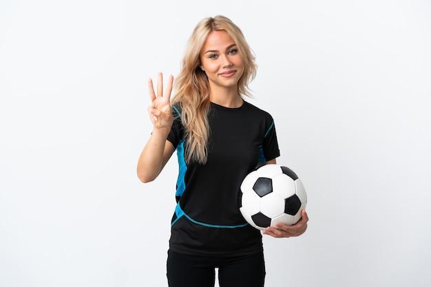 Junge russische frau, die fußball spielt, isoliert auf weiß glücklich und drei mit den fingern zählend