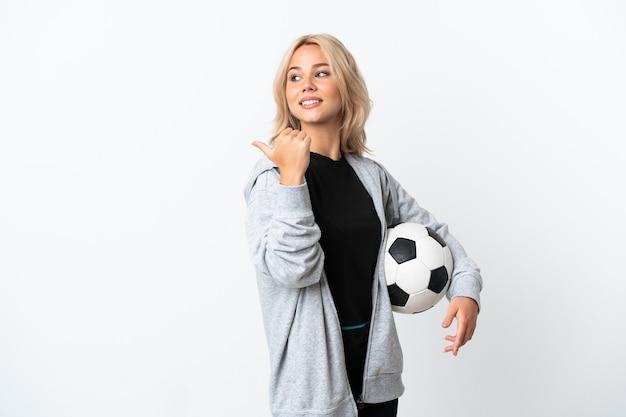 Junge russische frau, die fußball spielt, lokalisiert auf weißer wand, die zur seite zeigt, um ein produkt zu präsentieren