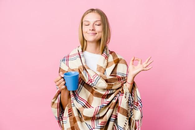 Junge russische frau, die in eine decke gewickelt ist, die kaffee trinkt, entspannt sich nach hartem arbeitstag, sie führt yoga durch