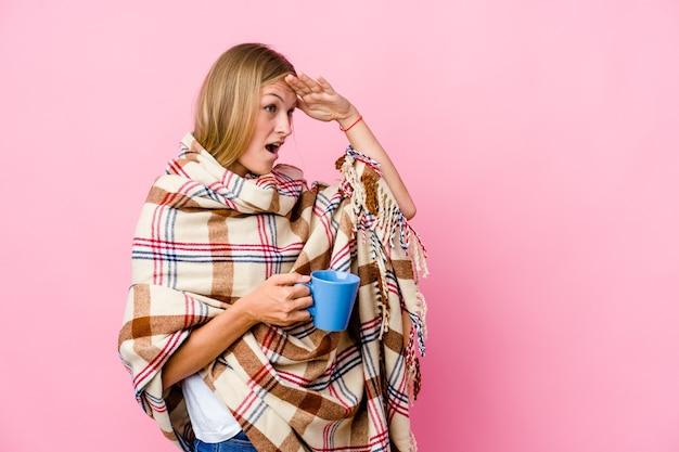 Junge russische frau, die in eine decke gewickelt ist, die kaffee trinkt und weit weg schaut und hand auf stirn hält.