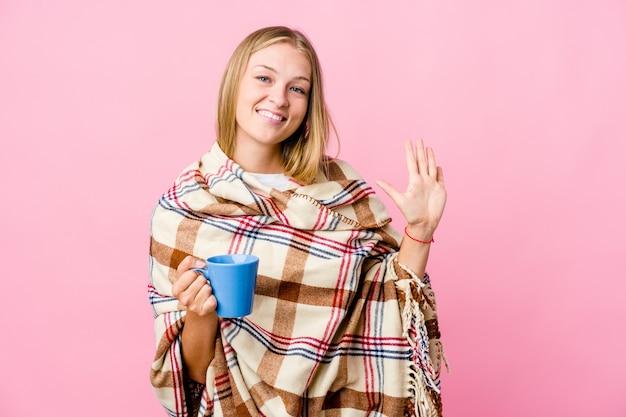 Junge russische frau, die in eine decke gewickelt wird, die kaffee trinkt, der fröhlich lächelt und nummer fünf mit den fingern zeigt.