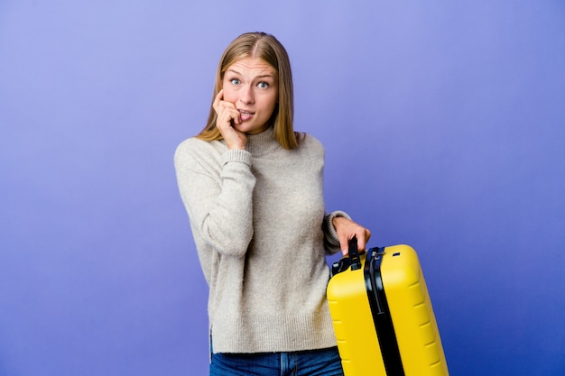 Junge russische frau, die koffer hält, um beißende fingernägel zu reisen, nervös und sehr ängstlich.