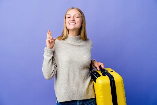 Junge russische frau, die koffer hält, um kreuzende finger für glück zu reisen