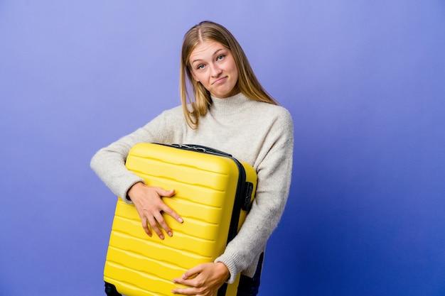 Junge russische frau, die koffer hält, um zu reisen, der sich sicher fühlt, arme mit entschlossenheit kreuzend.