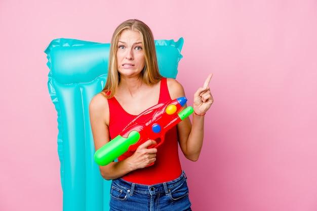 Junge russische frau, die mit einer wasserpistole mit einer luftmatratze spielt, die schockiert zeigt mit zeigefingern auf einen kopienraum zeigt.