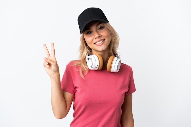 Junge russische frau, die musik lokalisiert auf weißem lächeln und siegzeichen lokalisiert hört