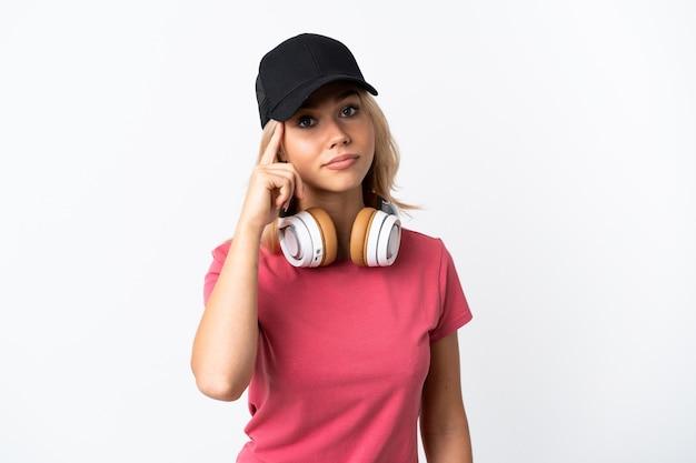 Junge russische frau, die musik lokalisiert auf weißer wand hört, die eine idee denkt