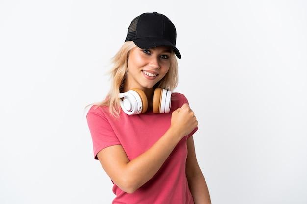 Junge russische frau, die musik lokalisiert auf weißer wand hört, die einen sieg feiert