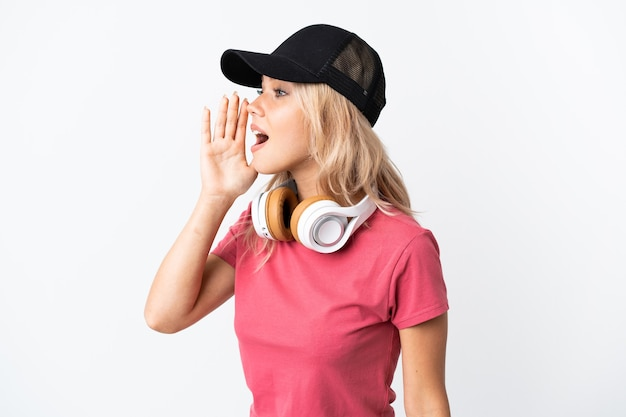 Junge russische frau, die musik lokalisiert auf weißer wand hört, die mit dem mund weit offen zur seite schreit