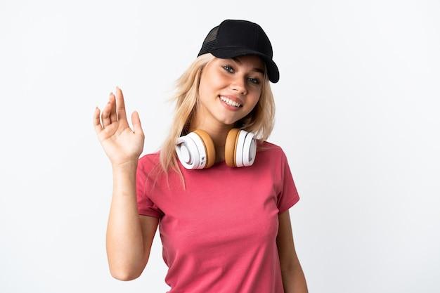Junge russische frau, die musik lokalisiert auf weißer wand hört, die mit hand mit glücklichem ausdruck salutiert