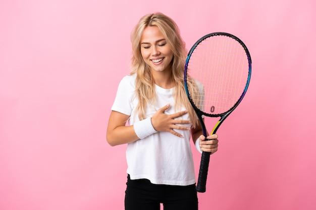 Junge russische frau, die tennis lokalisiert auf lila hintergrund spielt und viel lächelt