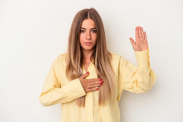Junge russische frau isoliert auf weißem hintergrund, die einen eid leistet und die hand auf die brust legt.