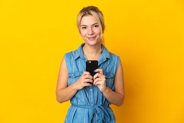 Junge russische frau lokalisiert auf gelbem hintergrund, der die kamera betrachtet und beim verwenden des handys lächelt