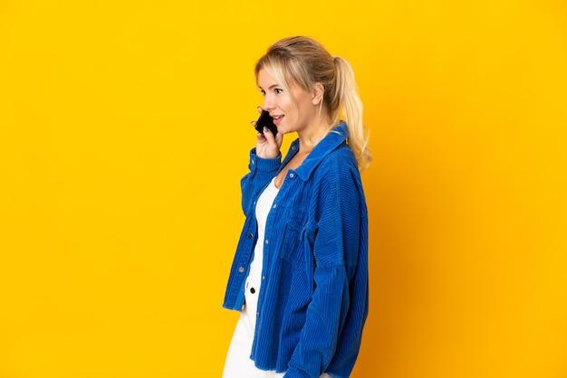 Junge russische frau lokalisiert auf gelbem hintergrund, der ein gespräch mit dem mobiltelefon mit jemandem hält