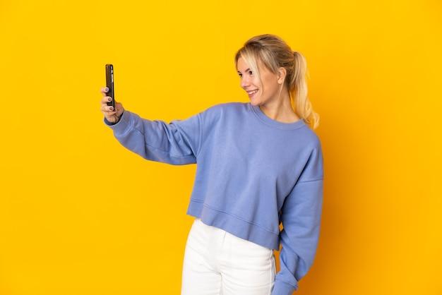 Junge russische frau lokalisiert auf gelbem hintergrund, der ein selfie macht