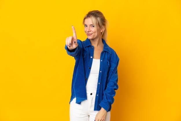 Junge russische frau lokalisiert auf gelbem hintergrund, der einen finger zeigt und hebt