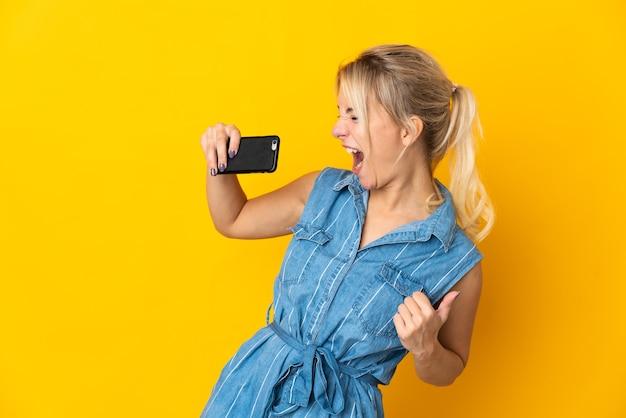 Junge russische frau lokalisiert auf gelbem hintergrund unter verwendung des mobiltelefons und des singens