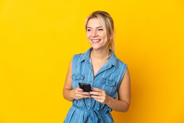 Junge russische frau lokalisiert auf gelbem hintergrund unter verwendung von mobiltelefon und nachschlagen