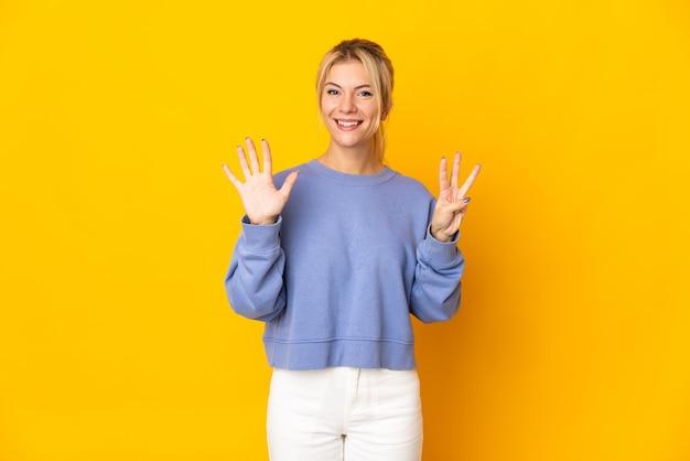 Junge russische frau lokalisiert auf gelber wand, die acht mit den fingern zählt