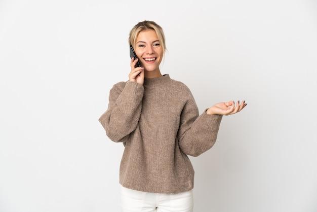 Junge russische frau lokalisiert auf weißem hintergrund, der ein gespräch mit dem mobiltelefon mit jemandem hält