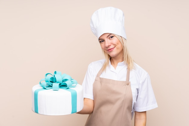Junge russische frau mit einem großen kuchen mit glücklichem ausdruck