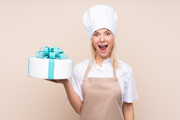 Junge russische frau mit einem großen kuchen mit überraschung und schockiertem gesichtsausdruck