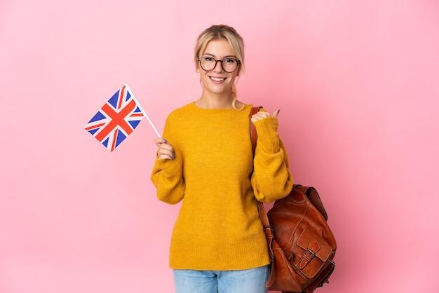 Junge russische frau mit einer flagge des vereinigten königreichs isoliert auf rosa hintergrund, die auf die seite zeigt, um ein produkt zu präsentieren