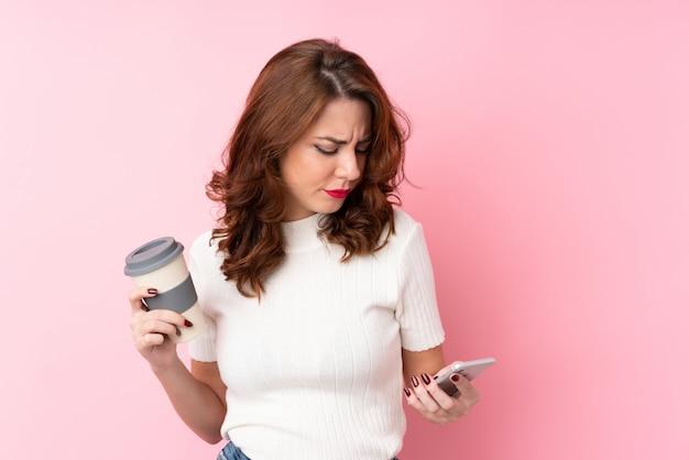 Junge russische frau über lokalisiertem rosa haltenem kaffee zum mitnehmen und einem mobile