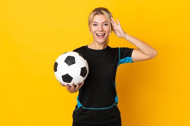 Junge russische fußballspielerfrau lokalisiert auf gelb mit überraschungsausdruck