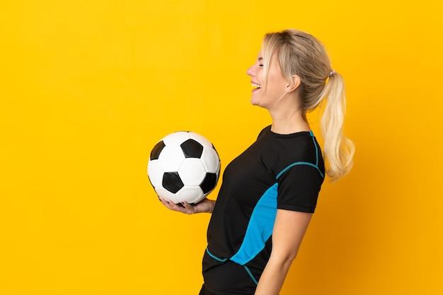 Junge russische fußballspielerfrau lokalisiert auf gelbem hintergrund, der in seitlicher position lacht