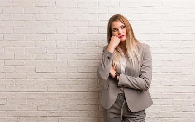 Junge russische geschäftsfrau, die an etwas, schauend zur seite denkt