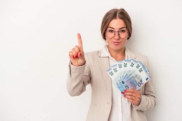 Junge russische geschäftsfrau, die banknoten lokalisiert auf dem weißen hintergrund hält, der nummer eins mit dem finger zeigt.