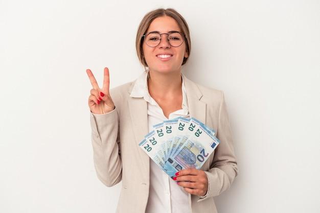 Junge russische geschäftsfrau, die banknoten lokalisiert auf weißem hintergrund hält, der nummer zwei mit den fingern zeigt.