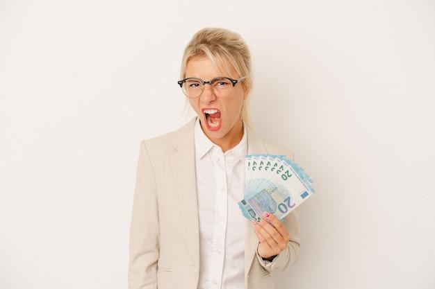 Junge russische geschäftsfrau, die banknoten lokalisiert auf weißem hintergrund hält, die sehr wütend und aggressiv schreien.