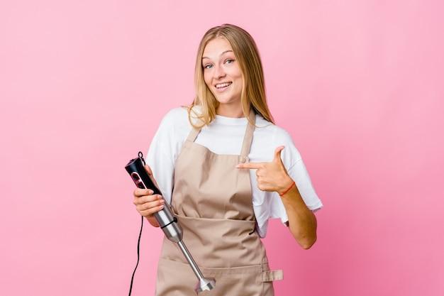Junge russische kochfrau, die eine isolierte person des elektromixers hält, die von hand auf einen hemdkopierraum zeigt, stolz und zuversichtlich