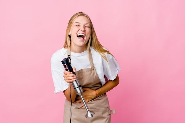 Junge russische kochfrau, die einen elektromixer isoliert hält, lacht glücklich und hat spaß, hände auf bauch zu halten.