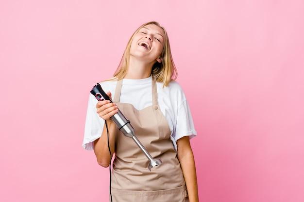 Junge russische köchin, die einen elektromixer isoliert isoliert und glücklich lachend hält, hals gestreckt zeigt zähne.