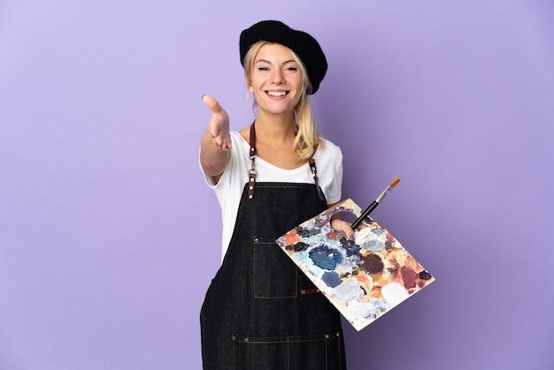 Junge russische künstlerin, die eine palette hält, die auf violettem hintergrund isoliert ist und sich die hände schüttelt, um ein gutes geschäft abzuschließen
