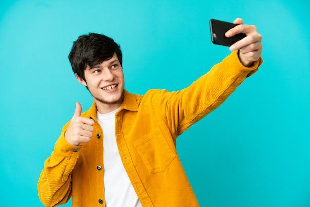 Junge russische mann isoliert auf blauem hintergrund macht ein selfie mit handy