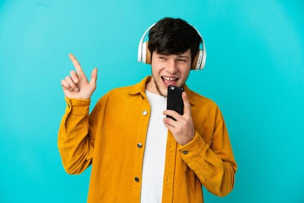 Junge russische mann isoliert auf blauem hintergrund musik hören mit einem handy und singen