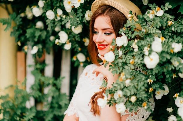 Junge russische schönheit. attraktives mädchen im weinlesetop und im gelockten roten haar und im strohhut, die für kamera mit zaun und grünen bäumen aufwerfen