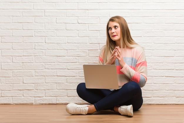 Junge russische studentenfrau, die einen plan ausarbeitend sitzt
