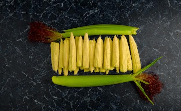 Junge saftige maiskörner auf einer dunklen oberfläche