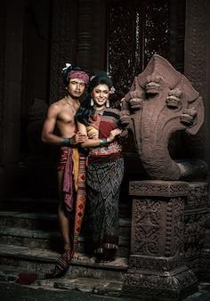 Junge schauspieler und schauspielerin tragen schöne alte kostüme, in alten denkmälern, dramatischen stil. spielen sie die beliebte legende der liebesgeschichte, das thailändische isan-märchen namens