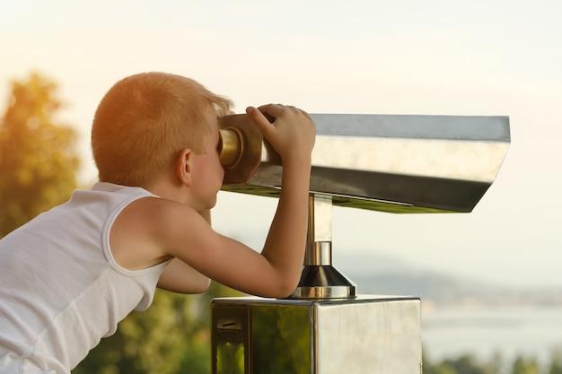 Junge schaut auf das große fernglas.
